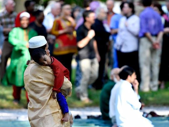 York community activists gather, at back, in support as members of Masjid Taw Heed gather for prayer marking the end of Ramadan at Brookside Park in Dover, Wednesday, July 6, 2016. Dawn J. Sagert photo