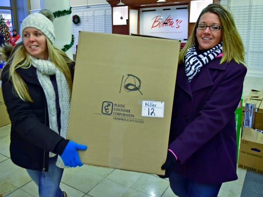 Tashia Caldwell and Tiffiny Ewan volunteer to help carry gifts during the Salvation Army Angle Tree event at Chambersburg Mall, Thursday, December 15, 2016.