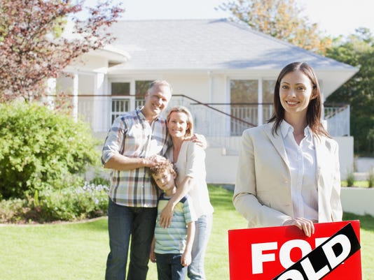 Realtor standing with family in front of new house