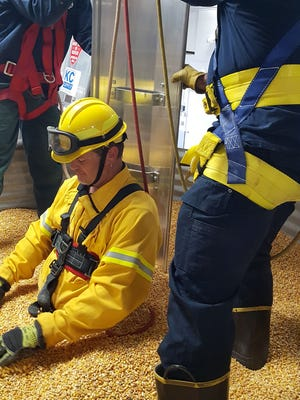 A flowing column of grain in a bin will pull a person down to knee level in 15 seconds and completely bury him or her in 30 seconds. Viroqua Fire Department members are pictured training on using a grain bin rescue device.