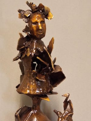 Bronze figures cast with lost wax method with copper hearts sitting on mahogany.