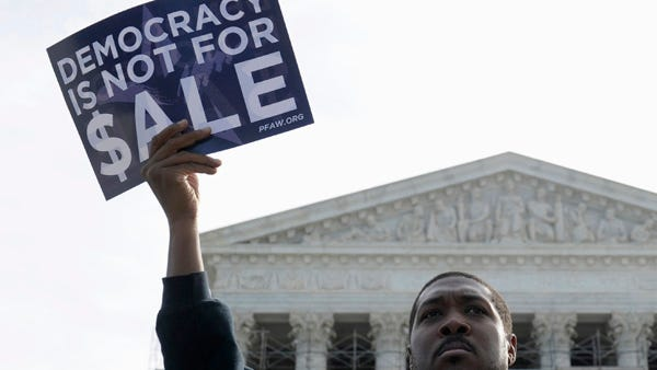 Cornell Woolridge of Windsor Mill, Md., takes part in a demonstration as the U.S. Supreme Court heard arguments on campaign finance.
