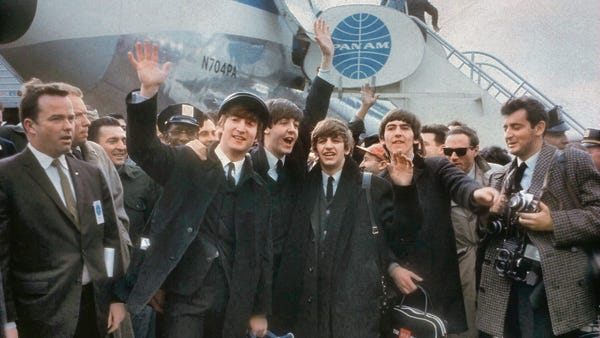 The Beatles wave to fans upon their arrival at Kennedy Airport on Feb. 7, 1964.