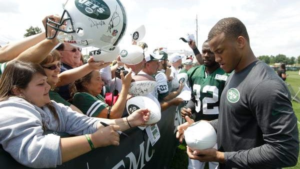 Jets cornerback Dee Milliner, right, signs autographs after practice during training camp on July 26 in Cortland.