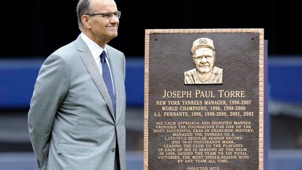 Joe Torre stands beside his plaque that will hang in Monument Park at Yankee Stadium on Saturday.