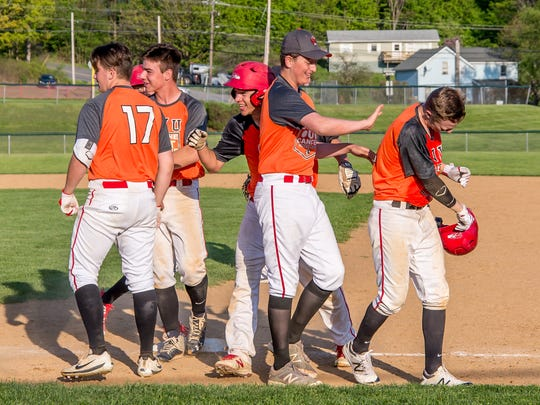 Champlain Valley sophomore Storm Rushford, second from right, celebrates with teammates his team's annual Strike Out Cancer Game on Thursday in Hinesburg.