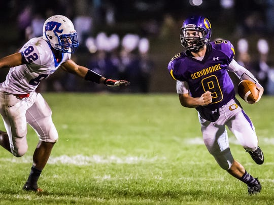 Oconomowoc quarterback Canton Larson (9) escapes Wisconsin Lutheran's Anthony Carver (82) in the backfield and turns upfield for a 51-yard touchdown run to end the second quarter on Friday, Sept. 27, 2013.