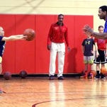 Edward McCants performs a running chest-pass drill with Emerson Williams, 8, at the McCants Reality Basketball class held at the gym at the Marion County Children Services campus in 2013.
