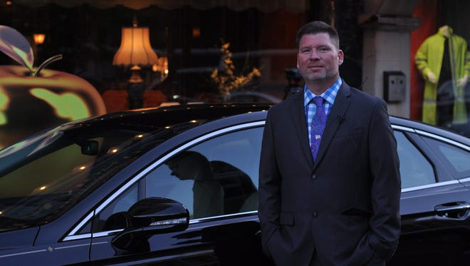 Russell Ballard stands next to his new 2016 Ford Fusion, which he won for being selected Golden Apple Teacher of the Year.