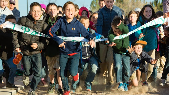 During the ribbon cutting ceremony for a new track at J Paul Taylor Academy, the students rip through the ribbon with excitement on Friday, February 2, 2018 at the school.