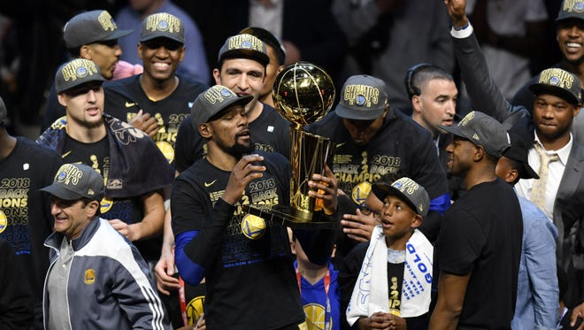Golden State Warriors forward Kevin Durant (middle) holds the Larry O'Brien Championship Trophy after defeating the Cleveland Cavaliers in game four of the 2018 NBA Finals at Quicken Loans Arena.