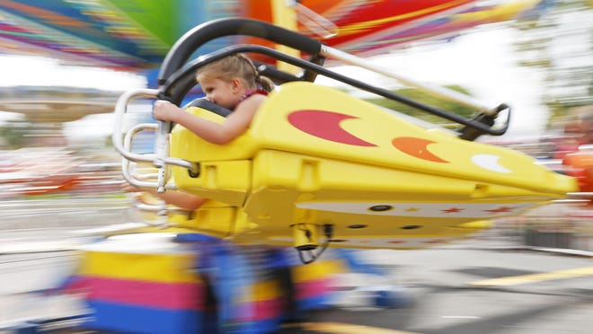 A young girl hangs on as she enjoys a ride at the Minnesota State Fair.
