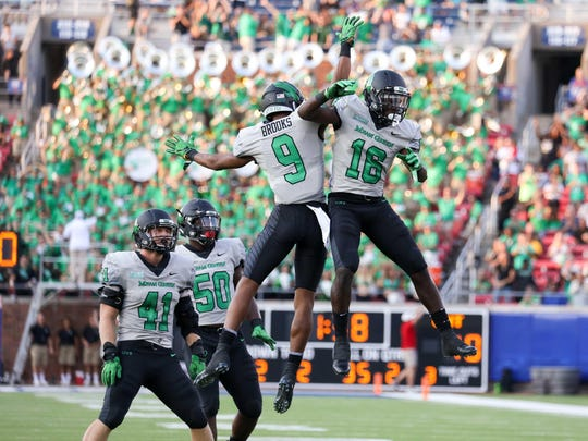 "North Texas players celebrate an interception in last week's 54-32 loss to SMU. The Mean Green deploy an ""Air Raid"" offense and average 580.5 yards a game."