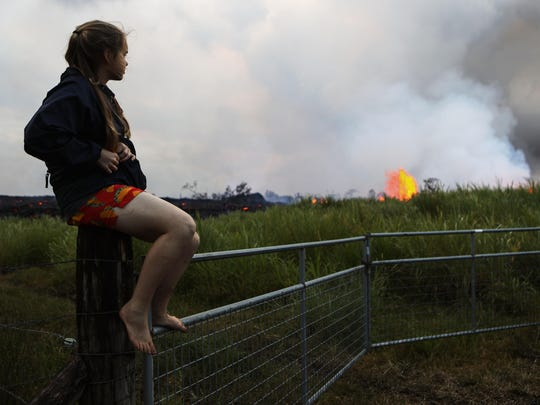 A young resident keeps an eye on lava from a Kilauea volcano fissure erupting and flowing near her home on Hawaii's Big Island on May 19, 2018 in Kapoho, Hawaii.