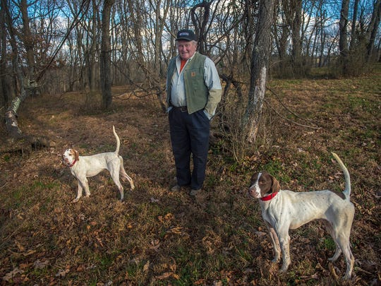Champion shooting dog handler George Tracy stands with English pointer Sugar Knoll Warpaint, left, and his son, Fast and Furious, on Nov. 24, 2015 near Tracy's home in Glenville.
