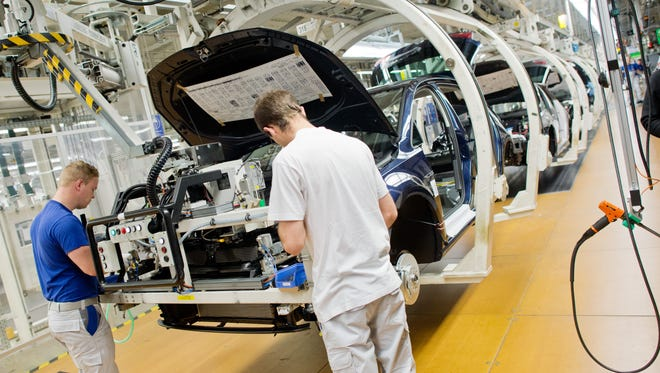 Employees work at  at the assembly  line for the Golf VII  at the  VW plant  in Wolfsburg, Germany Wednesday Oct. 21, 2015.  ( Julian Stratenschulte/Pool Photo via AP)