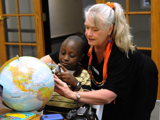 Bird Thomas, right, helps Espoir Sezerano, from Congo, take a photo of his native country on a globe at a weeklong PhotoVoice program at The Center for Contemporary Arts in March 2015.