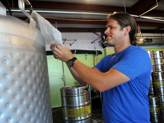 Lookout Brewing Co. owner John Garcia takes a look at what's in the tanks in his brewery.