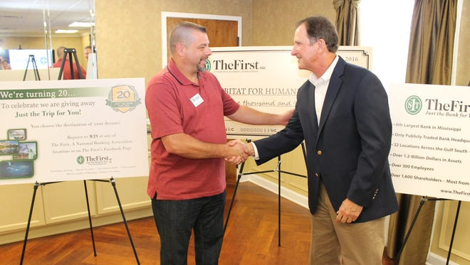 """The First CEO and President  M. Ray """"Hoppy"""" Cole presents a $ 5,000 check to Michael Pascarella, executive director of Hattiesburg Area Habitat for Humanity."""