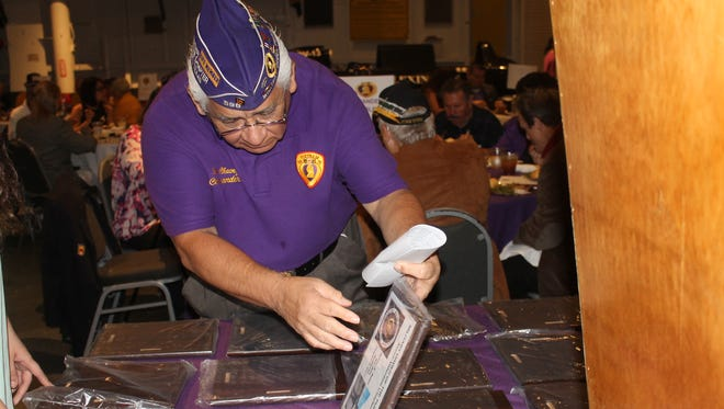 Ram Chavez examines the plaques made for Purple Heart recipients Tuesday, Feb. 28, 2017.