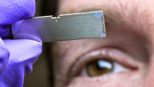 Andrew Cannon looks closely at a metal chip with microscopic
