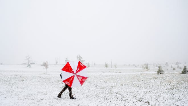 A man shields himself from the snow and wind in 2014 in Fort Collins.