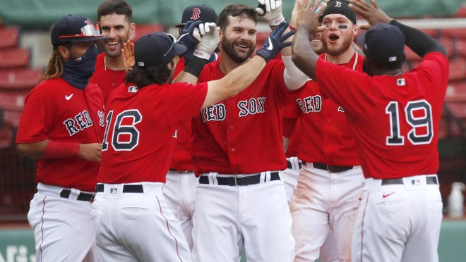 The Red Sox' Mitch Moreland, center, celebrates with teammates his two-run, walk-off home run in the ninth inning in Sunday's game against the Blue Jays.