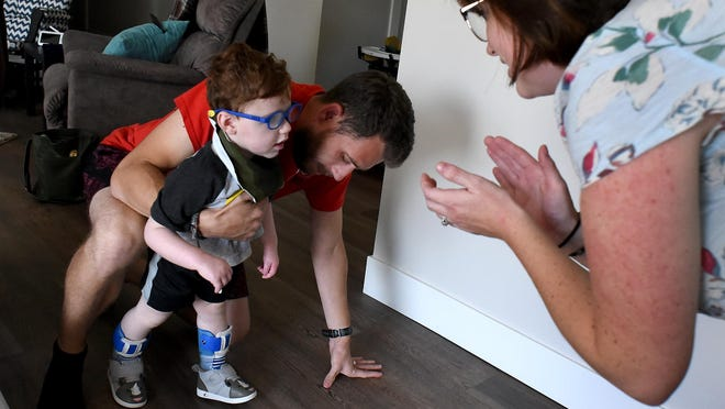 Lauryn Reau cheers on her son, Parker, who's almost 2 years old, as he practices walking with leg/foot braces. His father, Steve, supports him. Parker was diagnosed with a traumatic brain injury as a result of shaken baby syndrome.