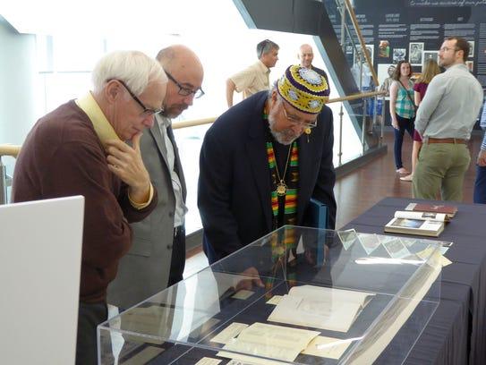 Francisco Mora-Catlett, right, looks through a display