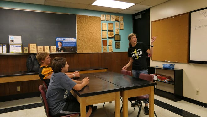 Baylee Knapp teaches agricultural concepts to Haven students Luke Hartung, 15, and Samuel England, 14.