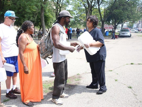 Assistant Pastor Earlene Edwards, right, is a part of the Greater Grace Street Outreach Ministry helping to serve lunch Wednesday, July 29, 2015, to more than 300 people in need who are gathering in Cass Park in Detroit for a service, a meal and fellowship.
