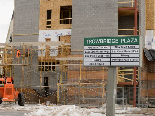 Construction workers put up some supports for the scaffolding Friday at the construction site for the Trowbridge Lofts apartments in the lot of the Trowbridge Plaza in East Lansing.