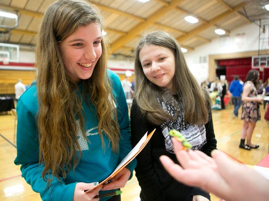 "St. Joseph's Catholic School eighth-graders Ashlyn Busche, left, and Kylah Wenzel, right, look at a red-eyed tree frog that Jean Boyles, not pictured, is holding from her store, Animal House of Marshfield, during the reality store at Spencer Middle School, Tuesday, March 10, 2015. Boyles was there as part of a pet stand where students were able to ""buy"" a pet."