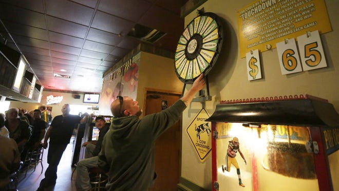Ray De Wall of Appleton gives a prize wheel a spin as Packer fans gather on game day at Lake Park Pub in Menasha.