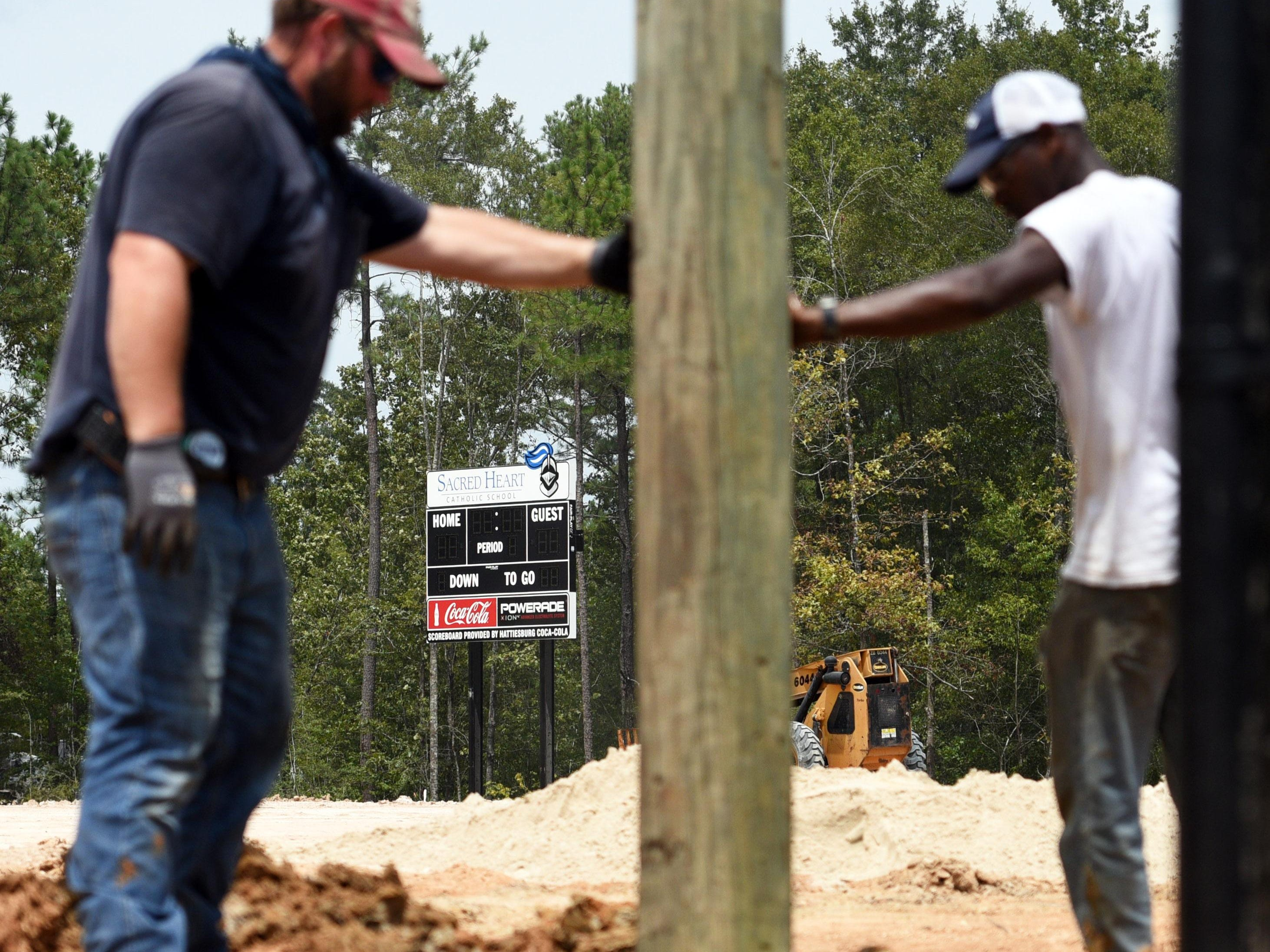 Doleac Electric Co. employees Thomas Simmons and Jamal McDonald work at the site of Sacred Heart's new football field on Friday afternoon. The poles will be used as the base structure for the press box.
