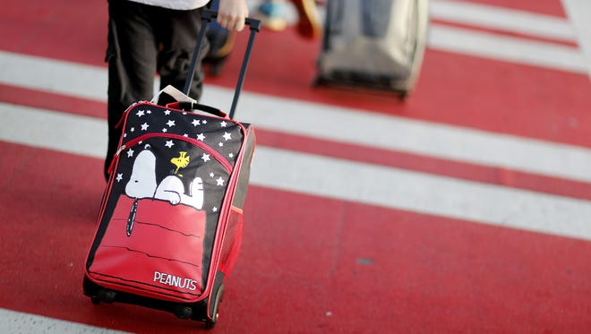 A child pulls a suitcase along a crosswalk upon arriving at Hartsfield-Jackson Atlanta International Airport ahead of the Thanksgiving holiday in Atlanta, Wednesday, Nov. 22, 2017.