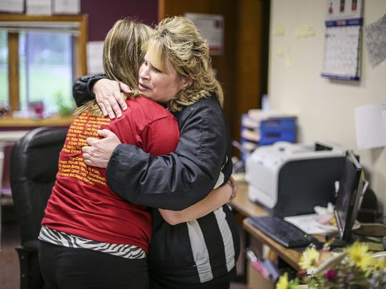Principal's secretary Allyson Thompson, right, hugs student Alexis Witham during the last day of classes Friday May 29, 2015, at Corwith in the Corwith-Wesley school district.