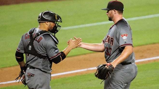 July 30, 2016; Los Angeles; Arizona Diamondbacks catcher Welington Castillo (7) and relief pitcher Jake Barrett (33) celebrate the 4-2 victory against Los Angeles Dodgers at Dodger Stadium.