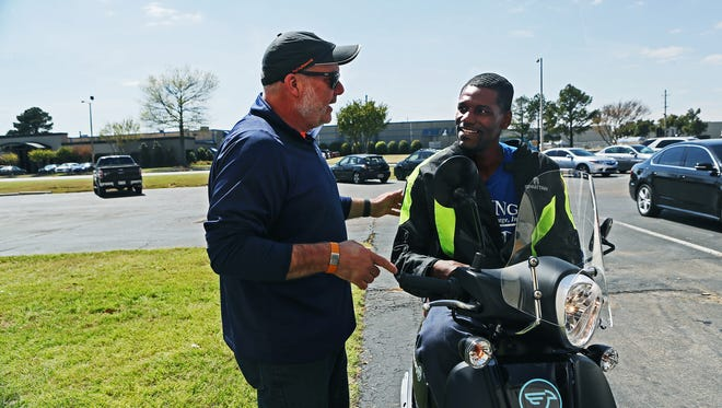 Andy Nix, left, president of My City Rides, talks to Charles Williams, a driver/mover for Ewing Moving & Storage, after delivering to him a new SYM Fiddle III motor scooter Thursday afternoon. The new nonprofit is beginning to deliver its first new motor scooters to Memphis workers who are signed up to buy them through payroll deduction. It's an effort to help remove lack of transportation as an obstacle to Memphis jobs.