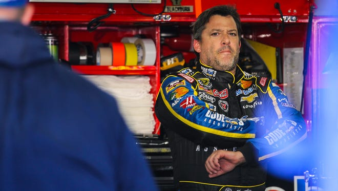 Driver Tony Stewart stands in the garage while his car gets serviced during practice for the NASCAR Sprint Cup auto race at New Hampshire Motor Speedway in Loudon, N.H., Friday, Sept. 19, 2014.