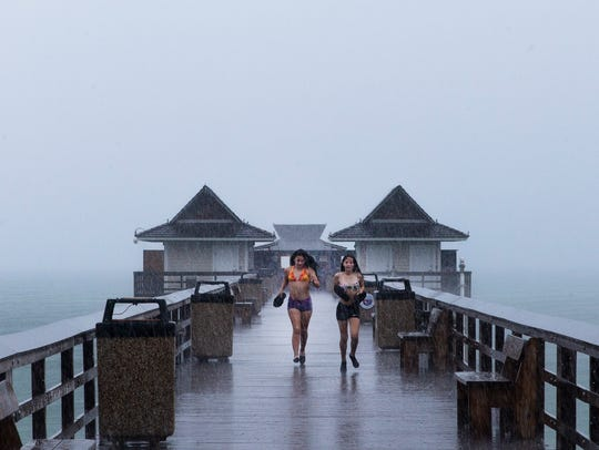 Two girls get caught in the rain at the Naples Pier