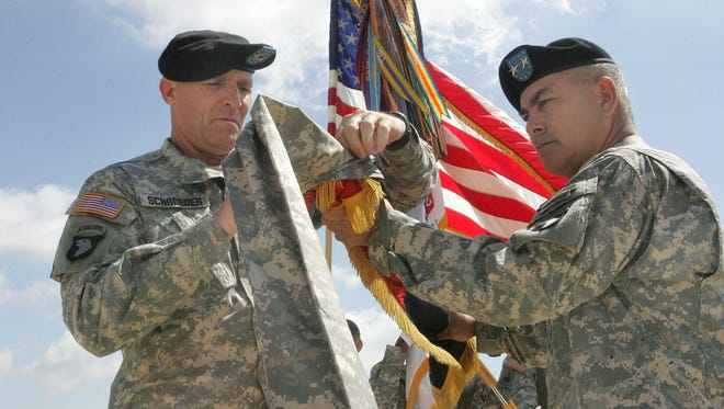 Then Maj. Gen. John Campbell, right, and Command Sgt. Maj. Scott Schroeder, left, case the 101st Airborne Division colors in May 2010 in front of McAuliffe Hall at Fort Campbell. Gen. Campbell has spent the last 18 months as the top commander for U.S. and allied forces in Afghanistan.
