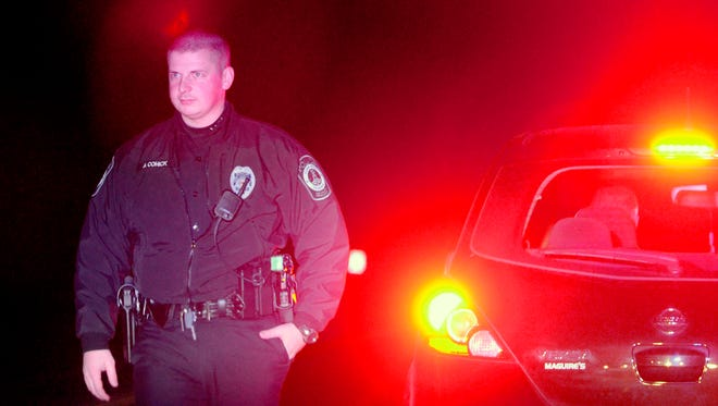In this file photo, York Area Regional Police Officer Adam Cohick returns to his car after completing a traffic stop on Windsor Road Thursday, February 2, 2012. Rep. Mike Regan, R-Dillsburg, sponsored a measure, House Bill 220, that would make it a third-degree felony for someone to get out of their vehicle after being stopped by police. John A. Pavoncello photo