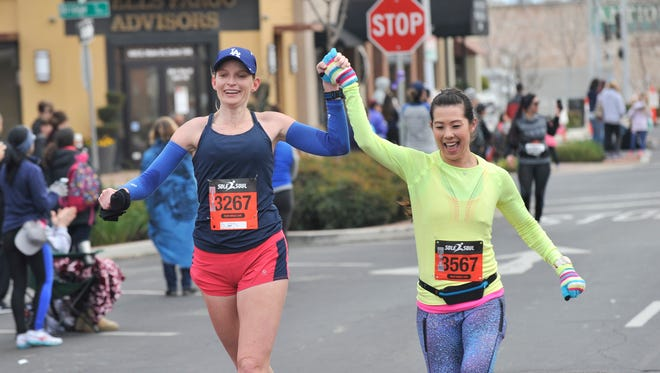 Amanda Whitten (left) and Stephanie Ormond finish together hands raised high during the Half Marathon during the 17th Annual End of the Trail Half Marathon & 10K in downtown Visalia in February 2017.