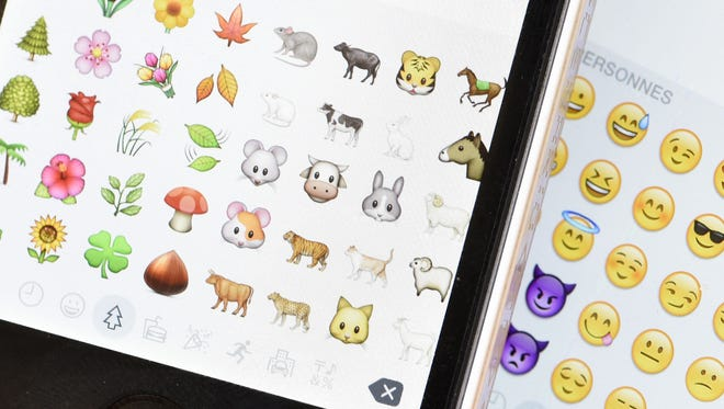 A picture shows emoji characters also known as emoticons on the screens of two smartphones.