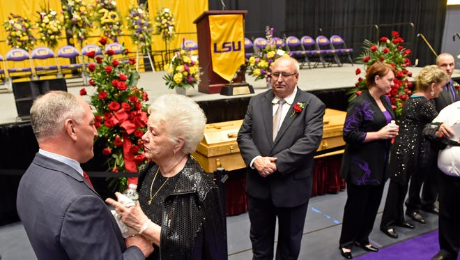 """Louisiana Gov. John Bel Edwards, left, meets with Dorothy """"Dot"""" Cannon during the visitation and funeral for former LSU football star Billy Cannon at Pete Maravich Assembly Center on the LSU campus Wednesday, May 23, 2018, in Baton Rouge, La. Cannon, a 1959 Heisman Trophy winner, died at his home early Sunday morning at the age of 80."""