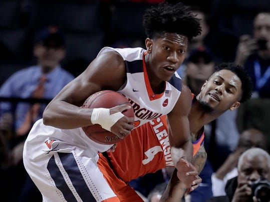 FILE - In this Friday, March 9, 2018, file photo, Virginia guard De'Andre Hunter (12) pulls down a rebound next to Clemson guard Shelton Mitchell (4) during the first half of an NCAA college basketball game in the semifinals of the Atlantic Coast Conference tournament in New York. Hunter, the ACC's sixth man of the year, will miss the NCAA tournament with a broken left wrist. The school says Hunter suffered the injury during the ACC tournament, but did not say how. (AP Photo/Julie Jacobson, File)