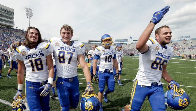 South Dakota State players Connor Landberg (18), Mitch Vejvoda (87), Alex Wilde (10) and Dallas Goedert (86) celebrate after their NCAA college football game against Kansas Saturday in Lawrence, Kan. South Dakota State won 41-38.