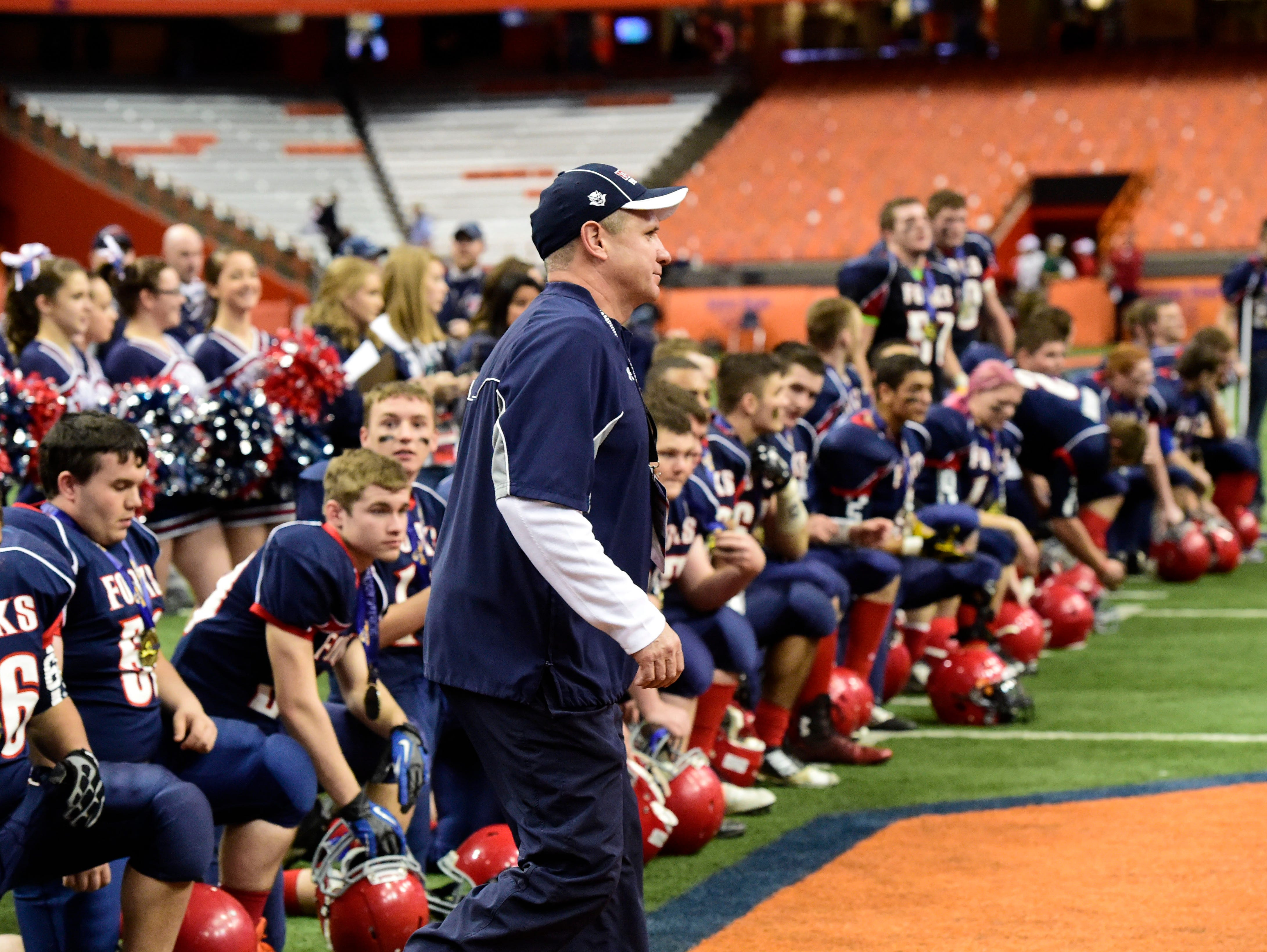 Chenango Forks head coach David Hogan goes to receive the trophy following the Blue Devils' Class C state championship on Nov. 29