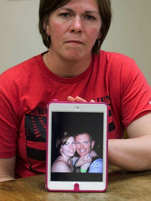 In this May 12, 2014 photo, Amy Miner, of Essex, Vt., poses in Burlington, Vt., with an April 2013 photo of herself and husband Kryn Miner, an Army veteran who suffered from Post Traumatic Stress Disorder, and who was shot to death by one of their children in April after threatening to kill the family. Amy Miner believes the Veterans Affairs health system must do more to help veterans who struggle with PTSD after returning home.